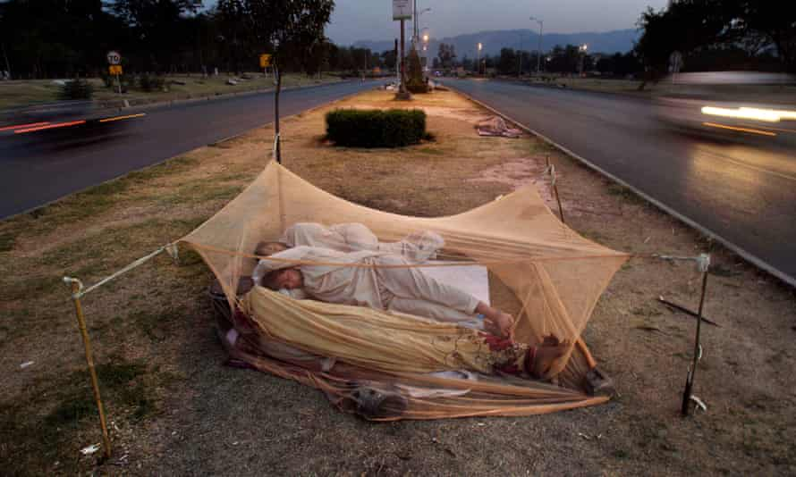 Pakistani labourers sleep under a mosquito net in the middle of a road in Islamabad.