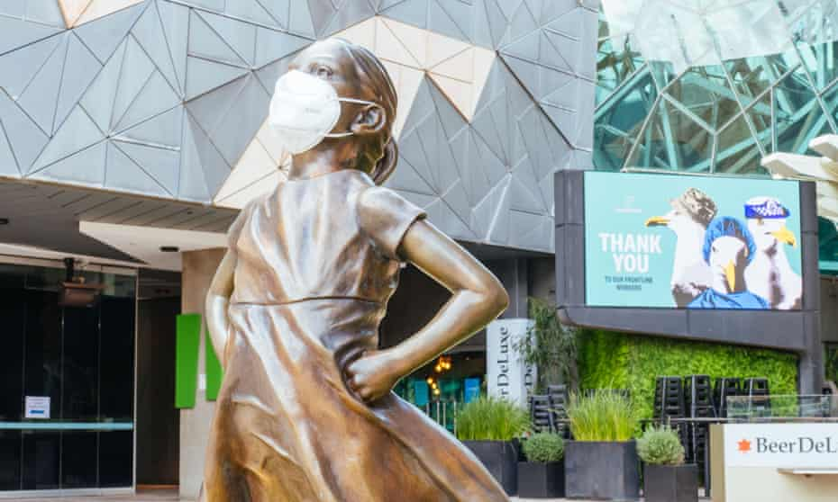The fearless girl statue in Federation square Melbourne wearing a mask
