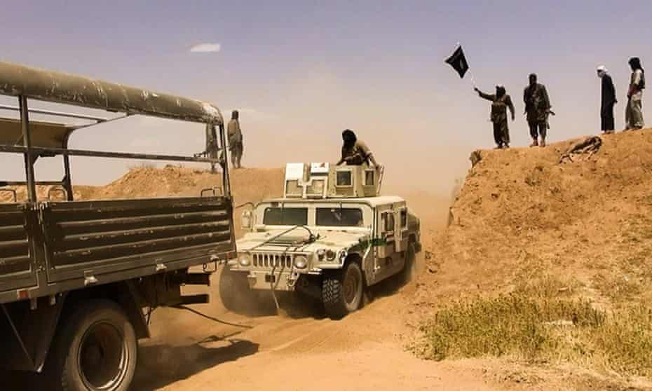 Isis militants waving a jihadi flag as vehicles drive on a new road through the Syrian-Iraqi border between the Iraqi Nineveh province and the Syrian town of Al-Hasakah, June 9 2014.