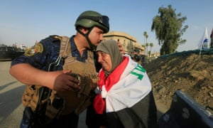 A member of Iraqi federal police kisses a resident of Mosul after 'victory' was declared over Islamic State.
