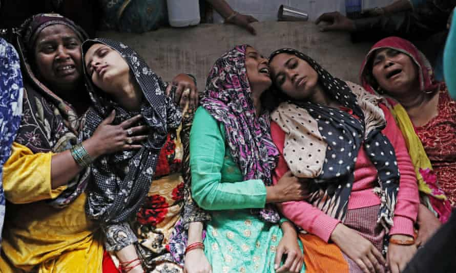 Mourning relatives of Hashim Ali, who died after being injured during the riots.