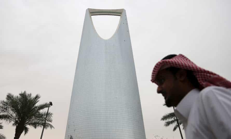 A man walks past the Kingdom Tower in Riyadh