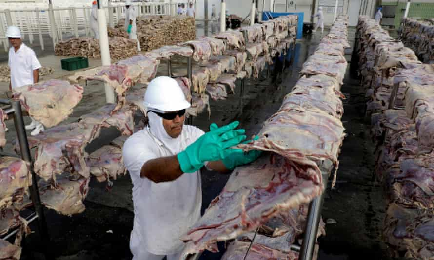 A JBS worker spreads salted meat for drying and packing at a plant in Santana de Parnaíba, Brazil.