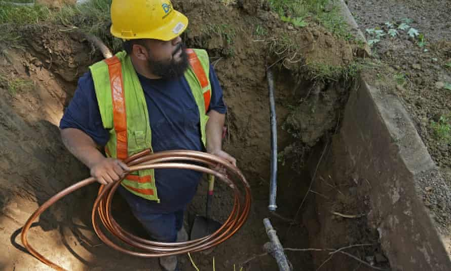 A worker in Denver, Colorado, installs a a new copper water service line.
