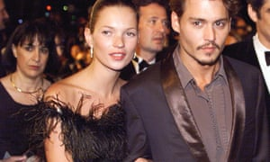 Kate Moss at Cannes in 1998, in a feathered black dress, accessorised by Johnny Depp.