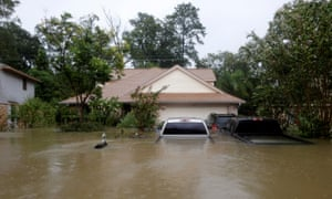 A house and cars partially submerged by flood waters from Tropical Storm Harvey in east Houston