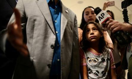 Estela Juarez, nine, with her sister Pamela as Congressman Darren Soto speaks at the airport.