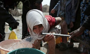 A girl drinks water from a well that is allegedly contaminated with cholera.