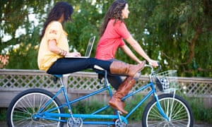 Two women riding a tandem bike while the woman on back uses a laptop
