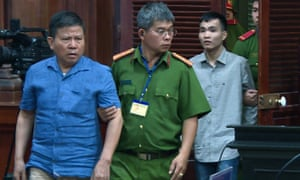 Chau Van Kham, left, is escorted to court in Ho Chi Minh City