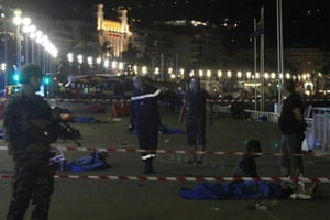 Soldiers, police officers and firefighters walk near victims covered with blue sheets on the Promenade