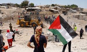 Palestinian demonstrators try to prevent an Israeli tractor from entering Khan al-Ahmar.