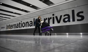 A passenger pushing luggage through the Arrival Hall of Terminal 5 at London's Heathrow Airport in January.