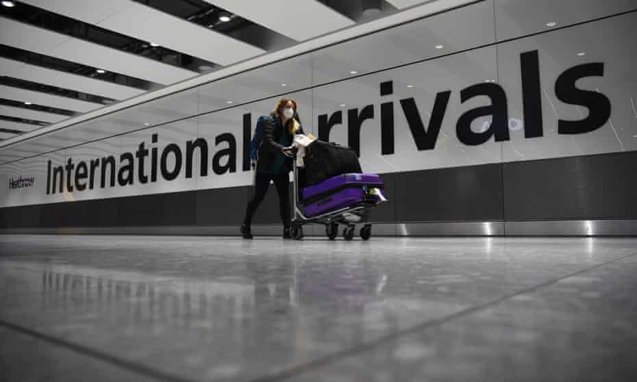 A passenger walks through Heathrow airport's international arrivals hall