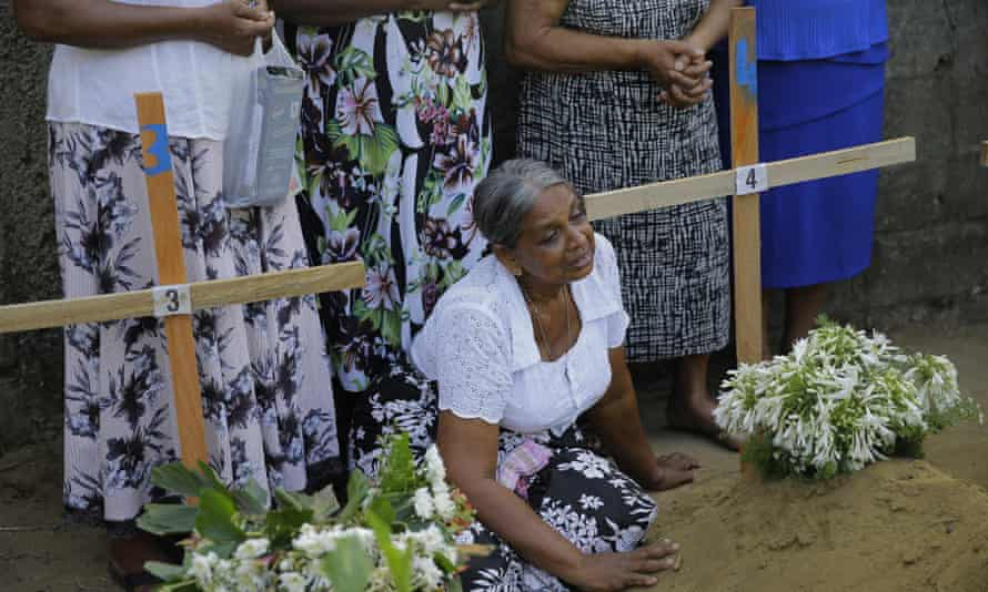 A Sri Lankan woman sits next to the grave of a family member in Katuwapitiya village, Negombo.