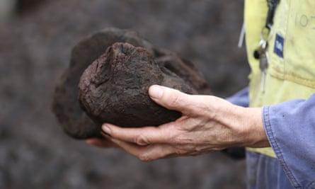 Man holds coal.