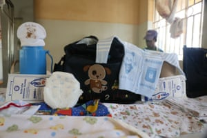Kemisa's bag: two nylon sheets, two pairs of gloves, a pair of new razor blades, cotton wool roll, washing soap powder, bottle of disinfectant, flask, cup, a roll of toilet paper, baby receiver to cover the baby, nappies, bedding,  money