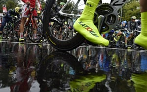 A sock of a rider from Russia's Katusha cycling team is reflected in the wet ground prior to the start of the stage