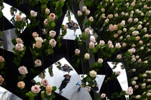 Visitors are reflected in one of the exhibits made from mirrors and roses hanging from the ceiling