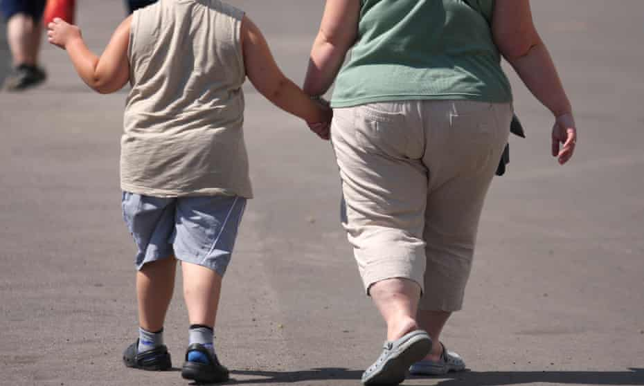 An overweight child and parent walking hand in hand