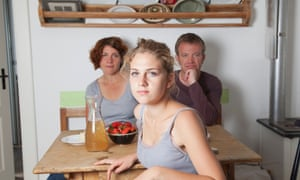 Young adult female in kitchen, with parents in background