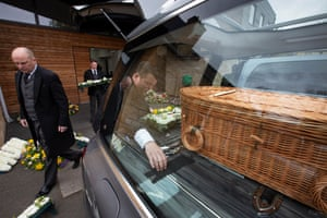 The funeral director Paul Brown along with funeral operatives Chris and Robert load Eddie's wicker coffin into a hearse