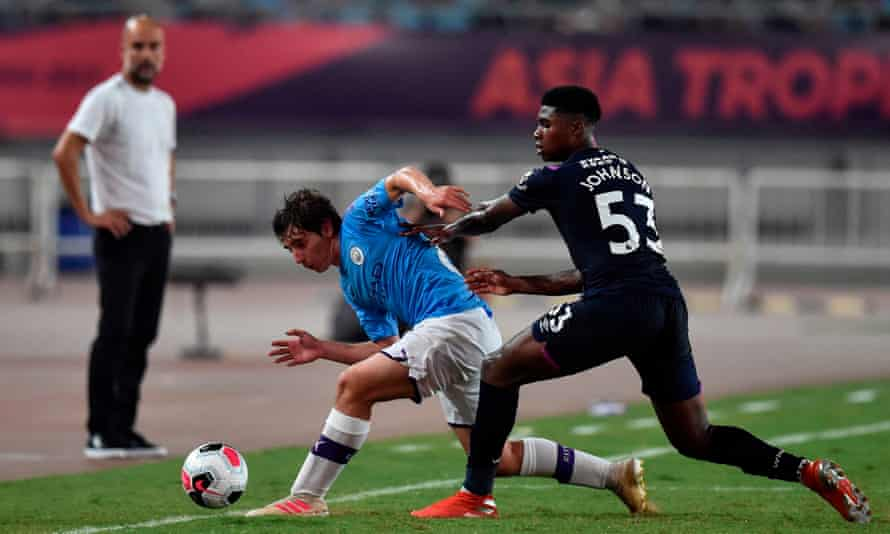 Manchester City's Adrián Bernabé battles for the ball as Pep Guardiola watches on.