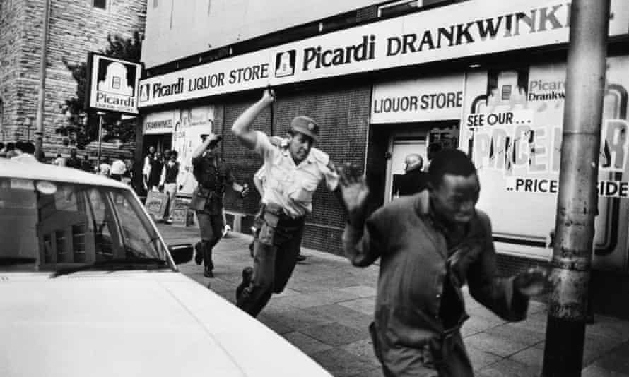 A South African police officer chasing a demonstrator with a sjambok whip