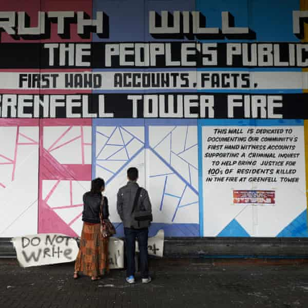 Pedestrians look at a mural in memory of the 72 victims of the Grenfell tower fire painted on a wall under the Westway flyover in London.