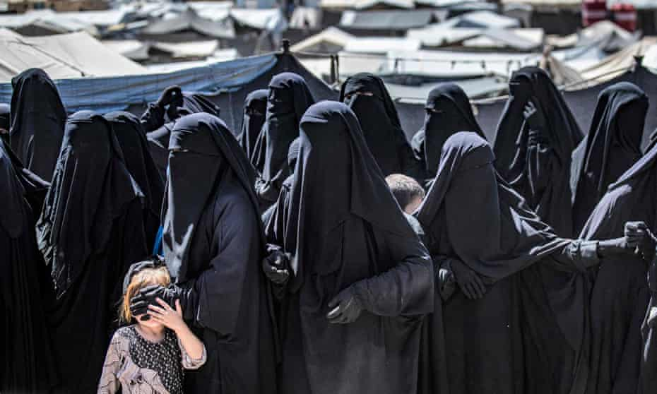 A group of women in black burqas in a queue, with one of them covering a small child's eyes with her hand