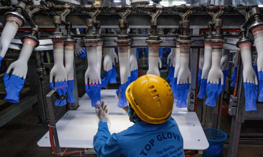 A worker inspects disposable gloves in August at the Top Glove factory production line on the outskirts of Kuala Lumpur, Malaysia.