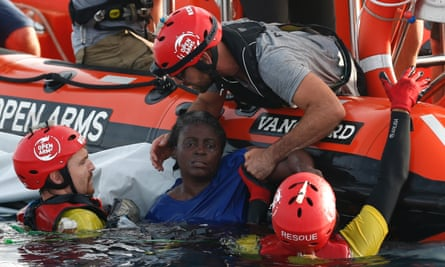 Members of the Spanish NGO Proactiva Open Arms rescue a woman in the Mediterranean