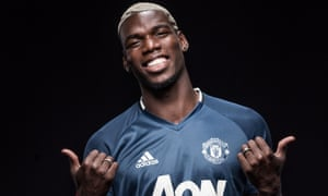 Paul Pogba poses after signing for Manchester United.