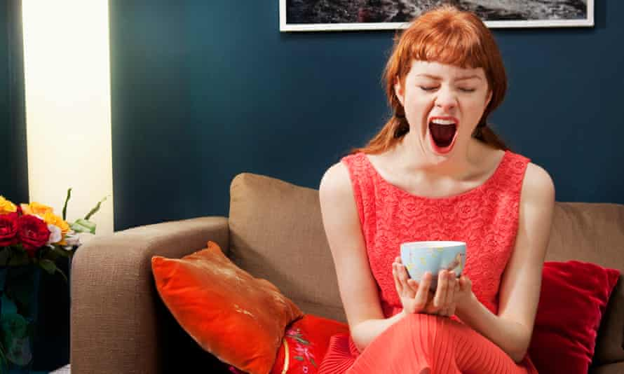 Woman sitting on sofa, holding a cup, yawning.
