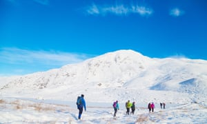 A group of walkers walking past Loch a' Choire on the way to the corbett Ben Vrackie near Pitlochry Scotland.