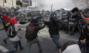 Protesters in Quito, Ecuador, storm police with a metal barrier over constitutional amendments by Rafael Correa allowing the indefinite election of presidents