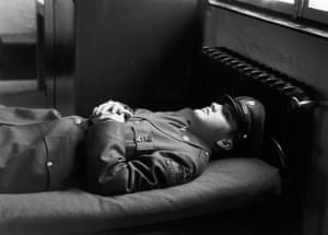 Presley wearing a military uniform, lying on an army cot with his hands folded across his chest, 10 January 1958