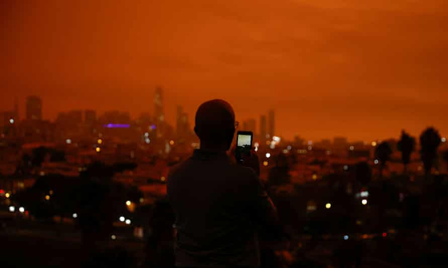 A man photographs Downtown San Francisco in Dolores Park under an orange sky darkened by smoke from California wildfires.