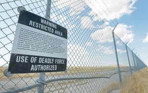 A warning sign authorizing the use of deadly force hangs on a fence line surrounding the facility