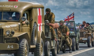 A convoy of military re-enactors in vehicles gather on the road to Arromanches, France.