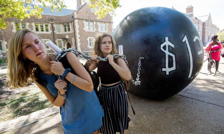 Students pull a mock ball and chain representing student debt, at Washington University in St Louis, Missouri.