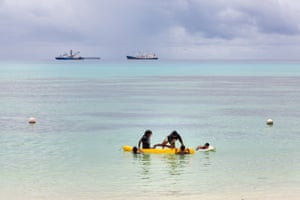 Children play in a small boat on the waters of the Funafuti lagoon