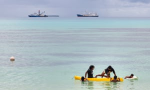 Children play in a small boat as large fishing boats sit offshore in Vanuatu