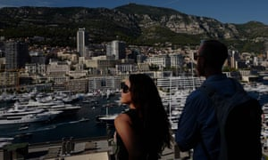 People look at yachts moored at the Hercules Port in Monaco.