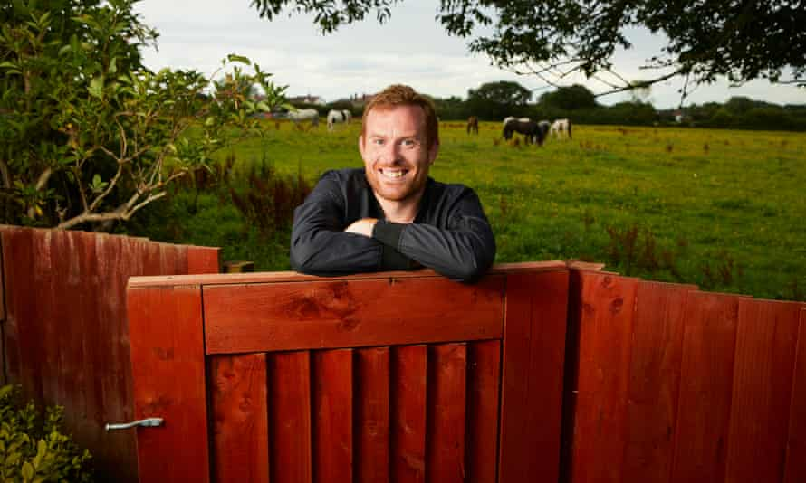 History teacher Tom Rogers opening a gate with field of cows behind