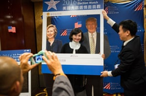 Taipei, Taiwan A woman poses for a photograph in front of cardboard cutouts of Democratic presidential nominee Hillary Clinton and Republican presidential nominee Donald Trump