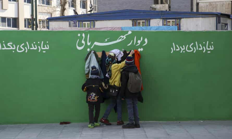 Youths check clothes hung on hooks at a 'wall of kindness' next to an underground station in central Tehran