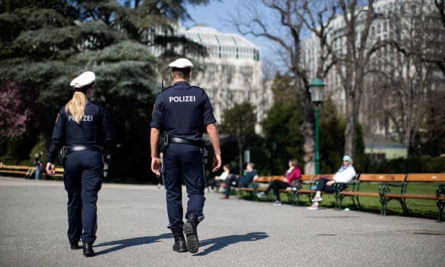 Police officers patrol a park in Vienna.