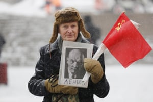 A man holds a portrait of the Russian revolutionary as he takes part in a flower-laying ceremony