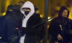 Armed police stand guard outside a building during a raid in Argenteuil on the outskirts of Paris.